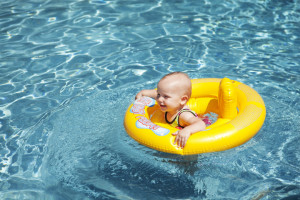 Baby in yellow raft in pool